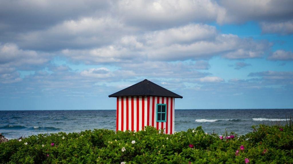 Rødstribet badehus på Rågeleje Strand med havet i baggrunden