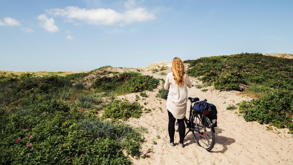 En kvinde står på en strand med en cykel.