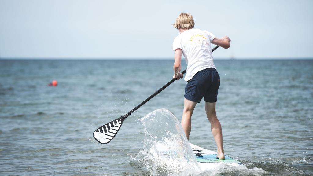 Dreng på SUP Stand Up Paddle Board på en vandet en sommerdag
