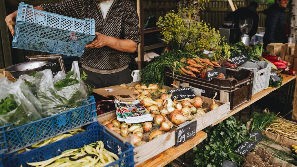 En mand flytter en kasse foran grøntsager på Torup Marked i Nordsjælland