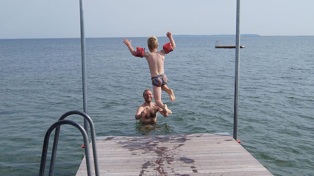 Far griber dreng i vandet ved Bogense Søbad