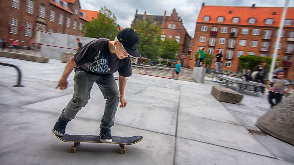 Dreng står på skateboard på skatebanen ved Rådhusparken