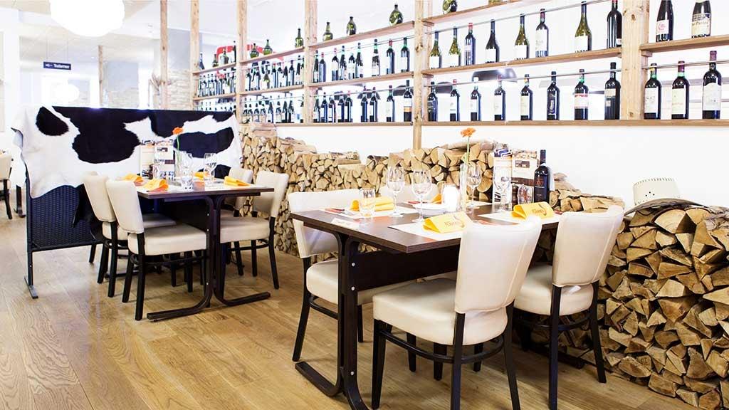 Indretning i Restaurant Flammen i Horsens med vinhylder og træ på væggene