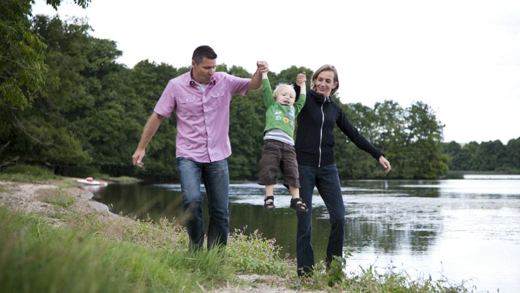 Familie går på stranden ved Mossø