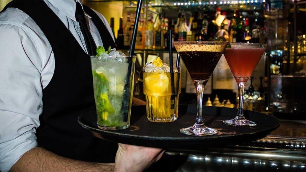 Tjener med drinks på Café Gertrud