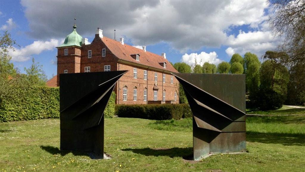 Herregården Hollufgård med skulptur i forgrunden