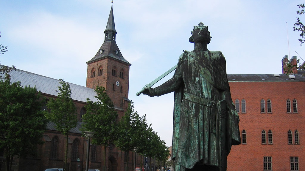 Skulpturen af Skt. Knud står ved Odense Rådhus og Odense Domkirke